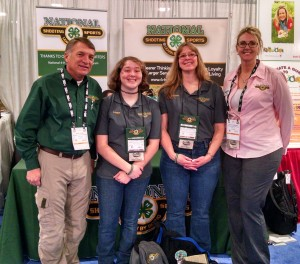 Members of the National 4-H Shooting Sports Committee, Dr. Mark Tassin of Louisiana State University (L) and Nicole Pokorney of the University of Minnesota (R) greet New York State 4-H Shooting Sports Teen Ambassador Logan Kimble-Lee (CL) and New York State 4-H Shooting Sports Instructor Colleen Kimble (CR) at the National booth at the 2016 SHOT Show in Las Vegas, NV.