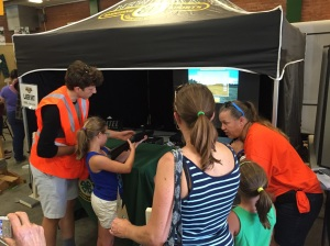 NYS4-HSS Instructor Denise Slocum (L), Yates County, with fairgoers at the Laser Shot Booth